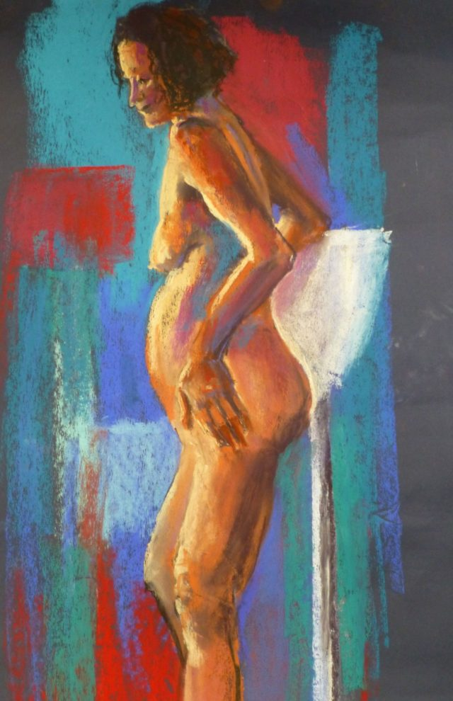 Julie Standing - A female life model standing amid an asymmetric coloured background - Pastel Painting