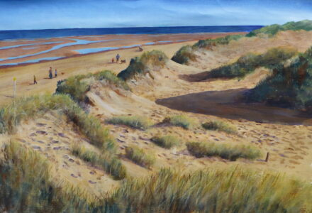 A view of the beach at low tide and the sand dunes and grasses lit by the morning sun at Formby point with dogwalkers and strollers walking on the beach