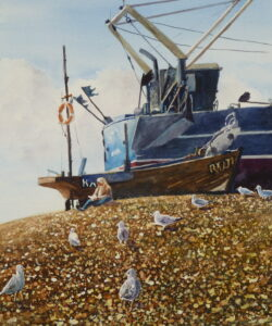 A figure seated on the shingle beach underneath the beached fishing boats eating a meal watched avidly by hungry gulls