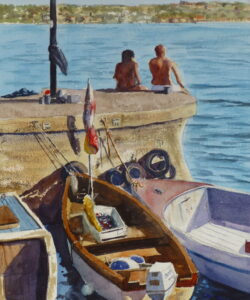 A couple sitting on a dock on Lake Garda surrounded by moored boats tied up as they enjoy the sunshine looking out at the view.