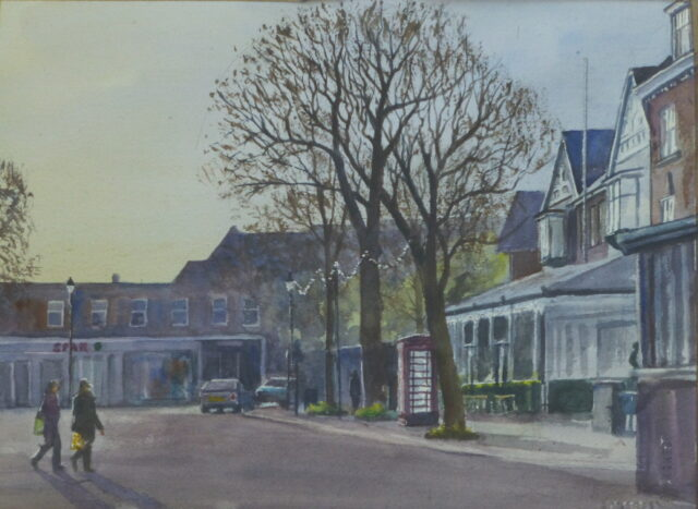 A watercolour painting of Birkdale Village, Southport in the early morning with people crossing the road in front of the old phone box which glows in the light.